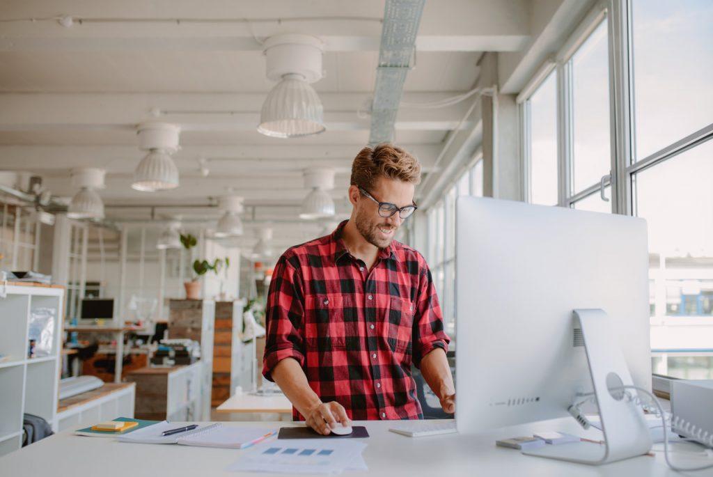 man working on desktop computer in modern workplace.