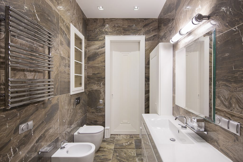 Dark Tiled bathroom with light over bathroom mirror