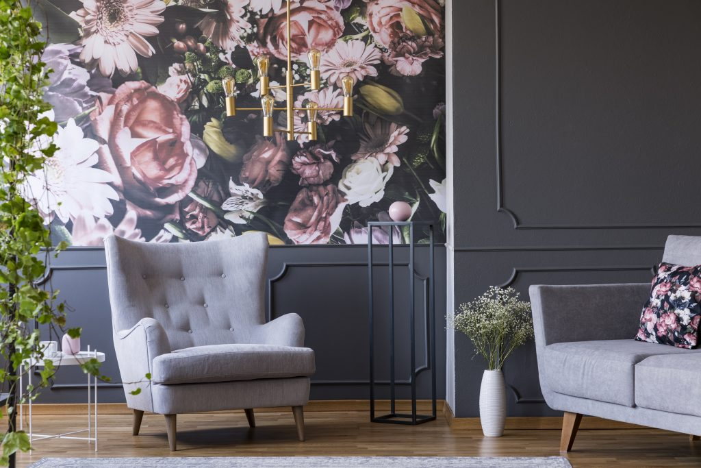 Grey armchair in living room with botanical wallpaper