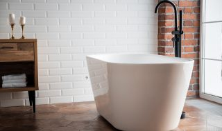 Large white bath with black stand alone taps