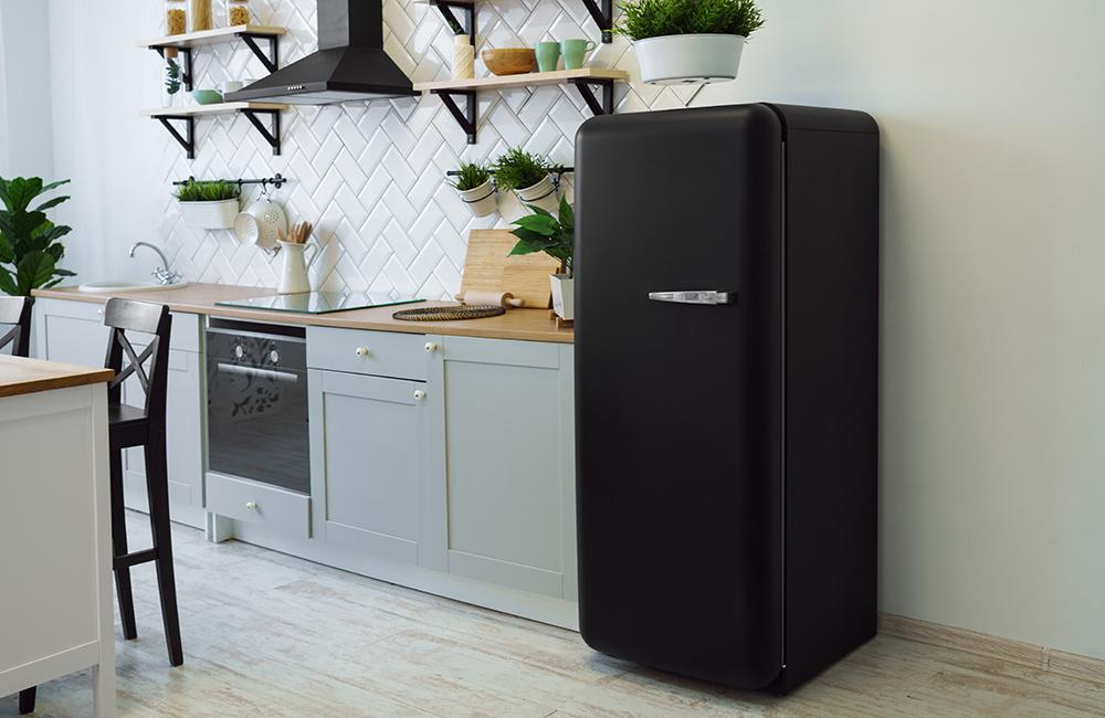 Retro style black fridge in gray wooden kitchen