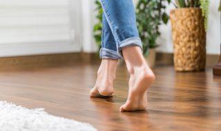 Women in blue jeans walking across wooden flooring