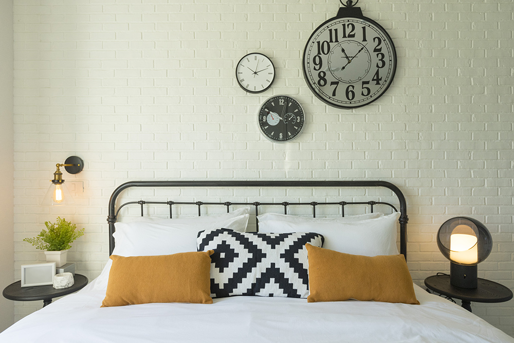 Metal bed with three decorative clocks on the wall