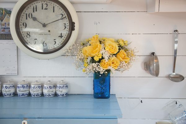 Rustic shabby chic kitchen with wall clock and yellow flowers in a blue vase