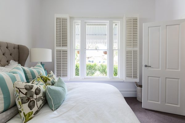 Stylish white bedroom with white shutters