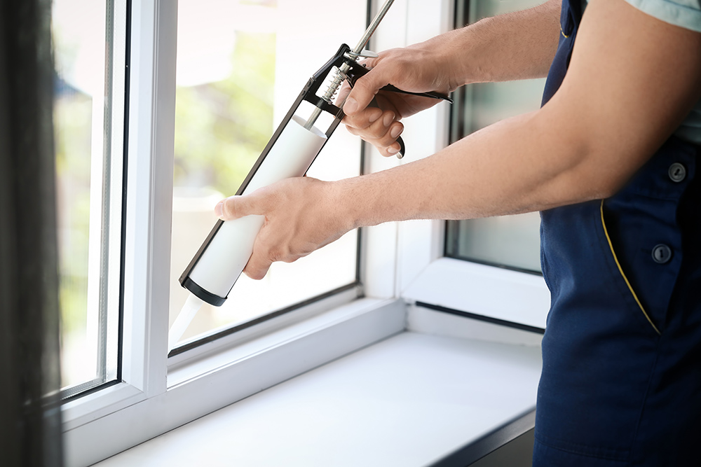Man sealling new windows