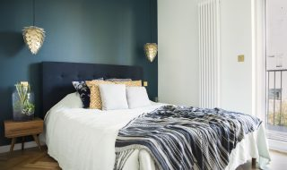 Blue and white small bedroom with wooden parquet flooring.
